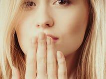 Cara sorprendida de la mujer que cubre su boca con la mano Foto de archivo libre de regalías