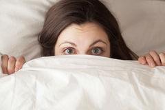 Cara sorprendida divertida de la cubierta de la muchacha con la manta blanca, headshot Imagenes de archivo