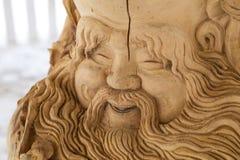 Cara tallada de un viejo hombre hecho de un árbol fotografía de archivo