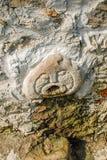 Cara tallada en el canalón de agua de piedra Foto de archivo libre de regalías
