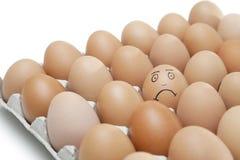 Cara triste dibujada en un huevo rodeado por los huevos marrones llanos en cartón contra el fondo blanco Foto de archivo