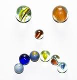 Cara triste dos mármores coloridos no fundo branco fotos de stock