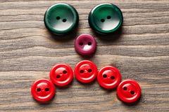 Cara triste feita de botões coloridos na tabela de madeira Fotos de Stock