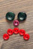 Cara triste feita de botões coloridos na tabela de madeira Foto de Stock