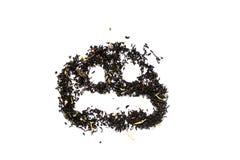 Cara triste hecha de la hoja de té negra en el fondo blanco Fotos de archivo libres de regalías