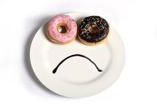 Cara triste sonriente hecha en plato con los anillos de espuma como ojos y boca del jarabe de chocolate en dieta y la nutrición d Imagenes de archivo