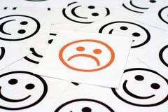 Cara triste y caras felices Fotografía de archivo libre de regalías