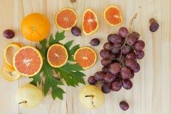 Cara winogrona i pomarańcze friut na drewnianym stole nad widok, Zdjęcia Stock