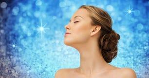 Cara y hombros de la mujer joven sobre luces azules Fotografía de archivo libre de regalías
