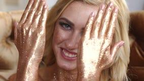 Cara y manos de la muchacha cubierta en polvo de oro metrajes