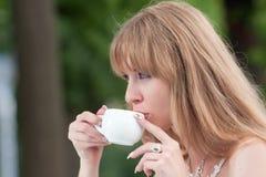Cara y taza de café de la muchacha Imagen de archivo