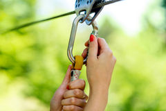 Carabine on a zip line. Female hands holding carabine on a zip line royalty free stock photography