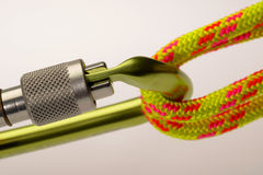 Carabiner and climbing rope. Closeup of a high quality carabiner attached to climbing rope with a plain background stock photography