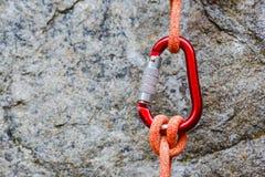 Carabiner con la corda su fondo roccioso Fotografia Stock Libera da Diritti