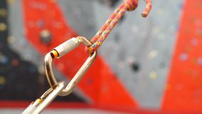Carabiner hook with a climbing rope on rocky background. Climbing concept. Carabiner hook with a climbing rope on rocky background. Climbing concept stock footage