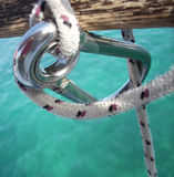 Carabiner. Metal carabiner with rope on barrier royalty free stock photography