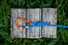 Carabiner and rope on a natural background. Carabiner on a climbing rope with a double overhand knot, on a natural background Royalty Free Stock Photography