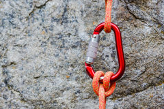 Carabiner with rope on rocky background. Climbing uquipment royalty free stock photo