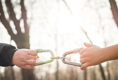 Carabiners for mountaineering in the hands of mother and child in nature. Connecting people Royalty Free Stock Photo