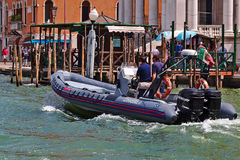 Carabinieri Motorboat with two men onboard in Venice, Italy. Venice, Italy - August 21, 2015: Carabinieri Motorboat (national military police of Italy) with two royalty free stock images