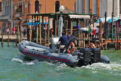 Carabinieri motorboat with two men onboard in Venice, Italy. Venice, Italy - August 21, 2015: Carabinieri motorboat (national military police of Italy) with two royalty free stock photography