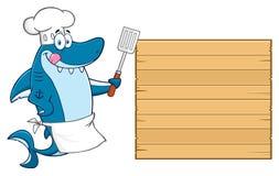 Caractère de mascotte de Blue Shark Cartoon de chef léchant ses lèvres et tenant une spatule sur le conseil vide en bois illustration stock