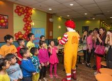 Caractère de Ronald McDonalds ayant la partie avec des fans Image libre de droits