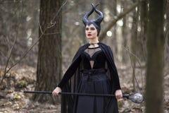 Caractère maléfique magique posant avec la forêt vide d'escroc au printemps photo libre de droits