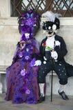 Caractères de carnaval de Venise dans des costumes colorés et des masques pourpres et noirs et blancs Venise de carnaval Images libres de droits