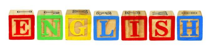 Caractères gras en bois orthographiant l'anglais au-dessus du blanc Photo stock