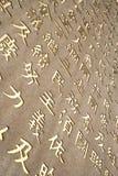 Caracteres chinos de oro tallados en la pared de piedra Imagenes de archivo