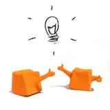 caracteres 3d anaranjados con la lámpara de la idea Fotos de archivo libres de regalías