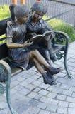 Caracteres de la historia de los hermanos de Grimms en un banco de parque Imágenes de archivo libres de regalías