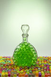 Carafe with colored balls. Carafe with A glass decanter with balls on a colored background and a light spotcolored balls Stock Photos