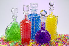 Carafe with colored balls. Carafe with A glass decanter with balls on a colored background and a light spotcolored balls Stock Photography