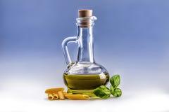 Carafe de bouteille en verre avec des feuilles de pâtes et de basilic de penne d'huile d'olive Photographie stock libre de droits