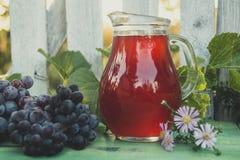 Carafe de vin rouge avec un groupe de raisins images stock