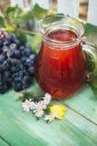 Carafe de vin rouge avec un groupe de raisins image stock