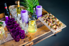A carafe of fruity beverage with rosemary and lemon and wooden tray of appetizers at a banquet on a decorated tea table. Beautiful Royalty Free Stock Photo