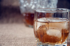 Carafe and glass of whisky, whiskey bourbon on a burlap, sacks background Stock Photography