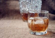 Carafe and glass of whisky, whiskey bourbon on a burlap, sacks background Stock Images