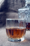 Carafe and glass of whisky, whiskey bourbon on a burlap, sacks background Royalty Free Stock Images