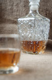 Carafe and glass of whisky, whiskey bourbon on a burlap, sacks background Stock Photo