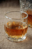 Carafe and glass of whisky, whiskey bourbon on a burlap, sacks background Stock Photos