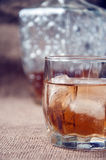 Carafe and glass of whisky, whiskey bourbon on a burlap, sacks background Stock Image