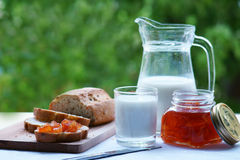 A carafe with milk and a glass of milk. Bread is cut on a wooden board. jar of Jam Stock Image