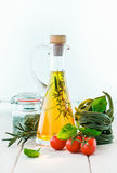 Carafe of olive oil. Fresh tomatoes and basil with uncooked green tagliatelle and a decanter or carafe of golden olive oil on a white painted wooden background Royalty Free Stock Images