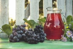 Carafe of red wine with a bunch of grapes stock images