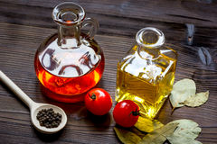 Carafes with oil and tomatoes on wooden background Stock Image