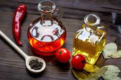 Carafes with oil and tomatoes on wooden background Stock Photo